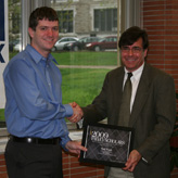 Falvey Memorial Library Director Joseph Lucia (right) presents Mark Woods with the Falvey Scholars Award.
