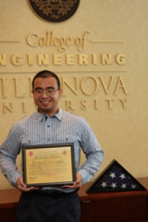 Thong Nguyen EE '06 presents an American flag and a certificate of authenticity signed by his commanding officer to the College of Engineering.