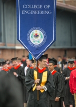 Matthew Brawley  '13 ECE carries the Engineering banner at Commencement