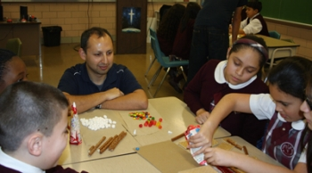 Villanova PhD student Sergio Yañez supervises the gingerbread house build.
