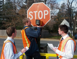 Evan Campbell,  James Matzke and Robert Flynn use a retroreflectometer to measure sign retroreflectivity