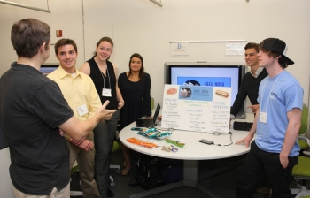"Second place team ""Born to Innovate"" discusses its ""Café Nova Express"" concept with II Luscri, director of the ICE Center."