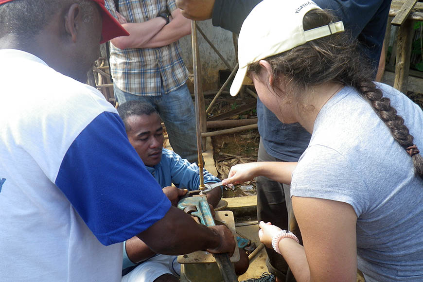 Stephanie Krakower '18 CE works on a broken hand pump with CRS engineer Jean Amie.