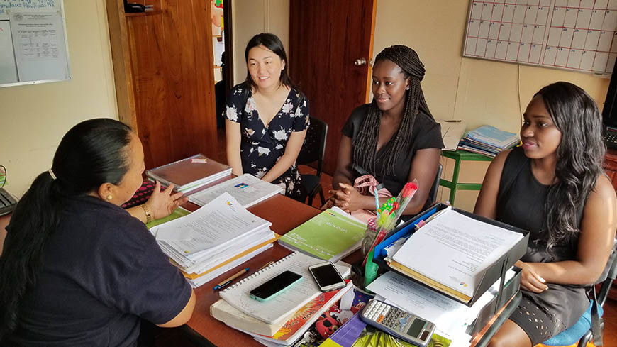 Senior Computer Engineering majors Sarah Chen, Gibel Sowe and Karol Pierre discuss a computer lab and computing education curriculum with the principal of a local school.