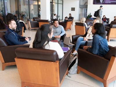 students sitting and chatting in law school commons