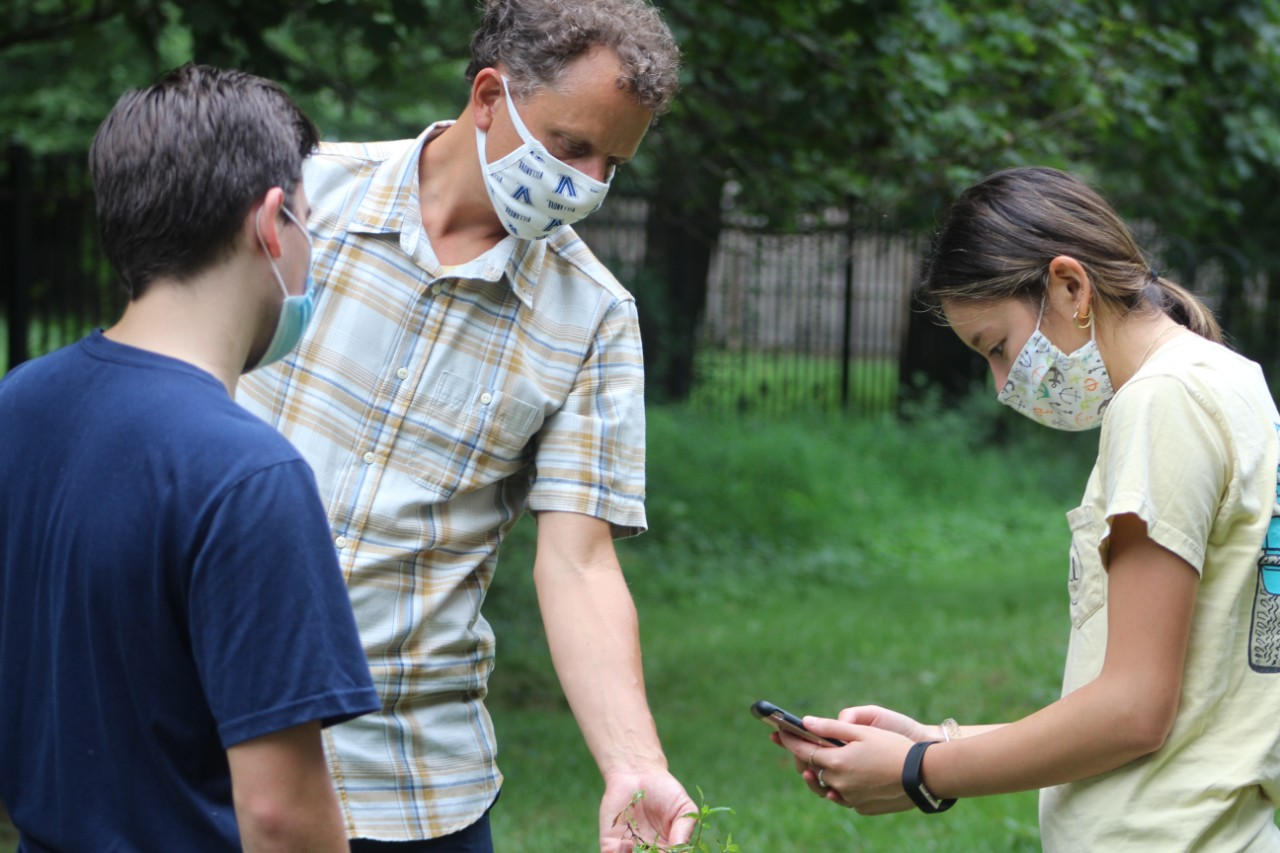 Adam Langley is in the center, wearing a cloth medical mask and a yellow checkered shirt. He holds out a tuft of grass, that the student to his left is taking a photo of with her phone. On Adam's right is a nother student looking on.