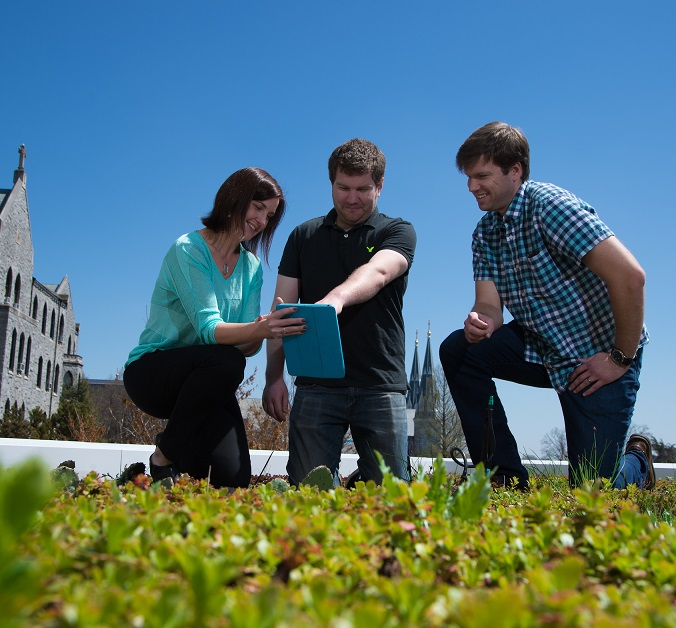 Engineering professor Bridget Wadzuk talks with colleagues on the Center for Engineering Education and Research Green Roof.