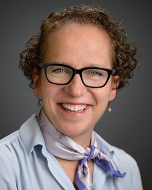 A photo of Dr. Judy Giesberg from the shoulders up. Judy wears a blue button down shirt with a jaunty purple silk scarf tied around her neck. She is smiling.