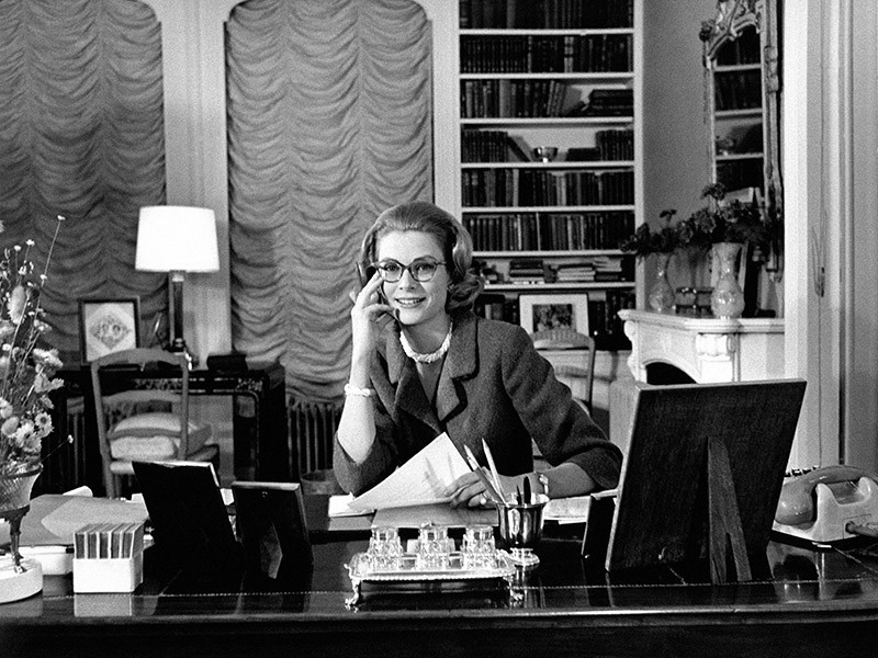A black and white photo of Princess Grace sitting at her desk with her hand on her cheek. She is wearing a blazer and a set of pearls.