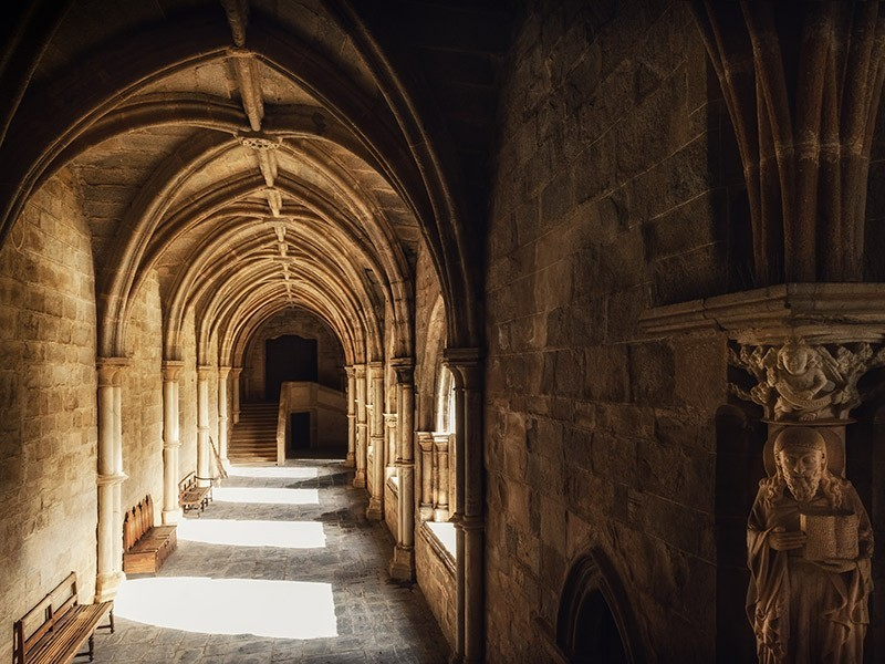 A photo of a row of cloisters with cathedral ceilings. Sun filters through the openings.