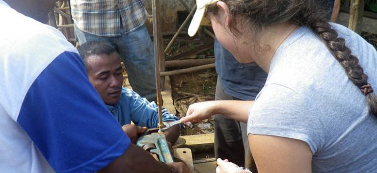 student works on a broken hand pump in Madagascar