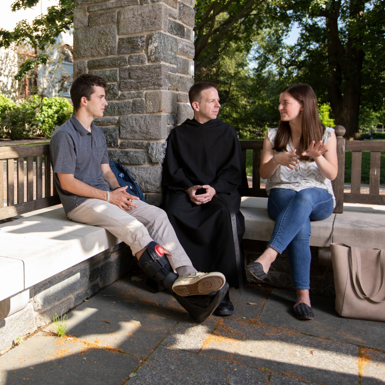 Father Kevin talks to two students in grotto