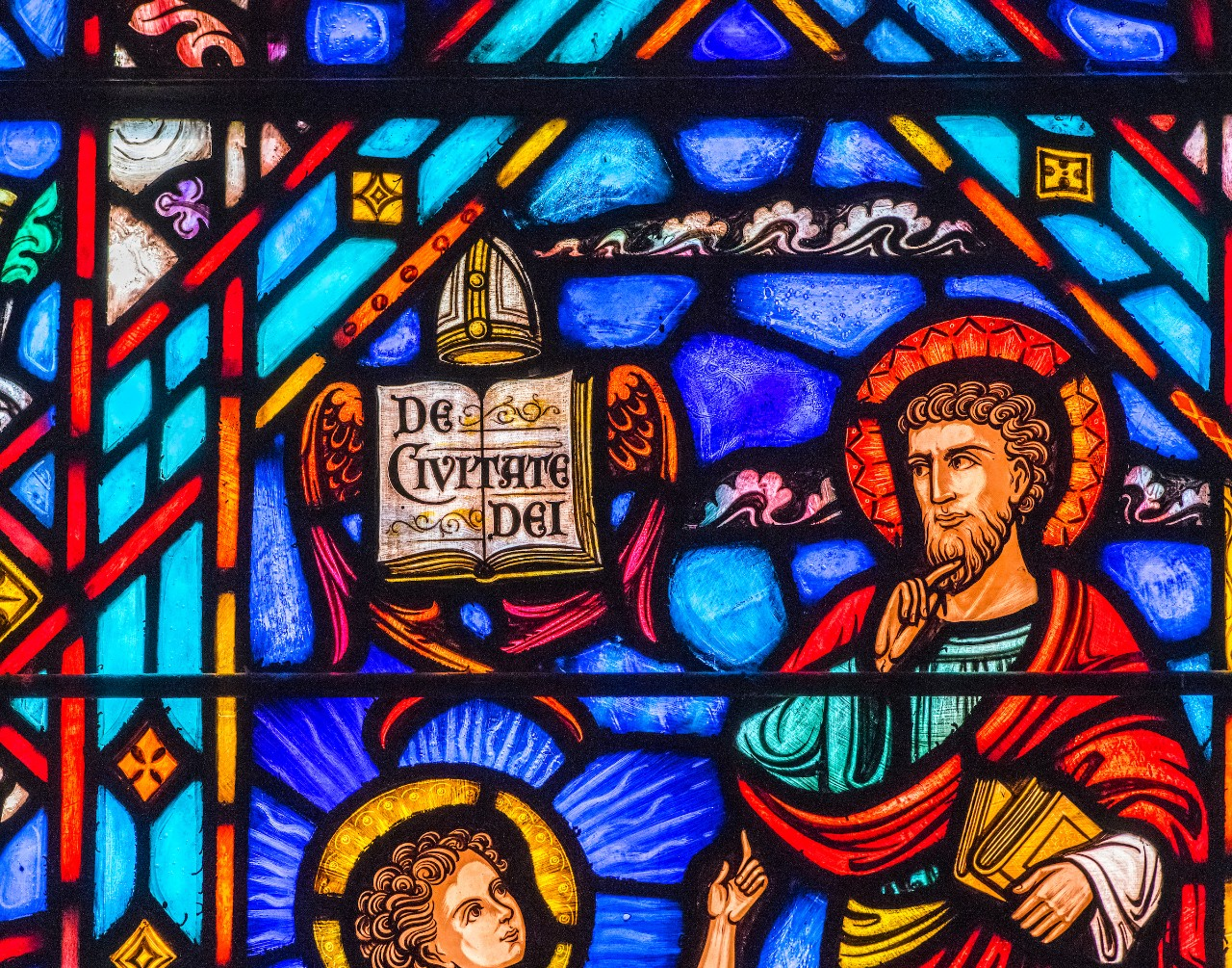 "stained glass windows showing Agustine and his volume ""City of God"""