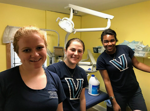 Three Villanova Nursing students at a foot care clinic for homeless clients which they run as part of their work with Nursing without Borders.