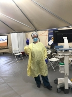 Female nurse wearing PPE in a tent.