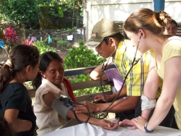student takes blood pressure of woman in nicaragua