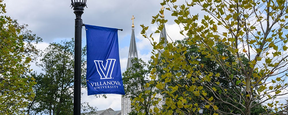 "A View of the Villanova ""V"" logo on a blue flag banner with St. Thomas of Villanova Church in the distance"