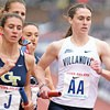 Villanova runner carrying a baton leads a pack at the Penn Relays