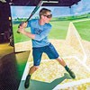 Baseball player wears VR goggles  in virtual reality CAVE and stands with bat in ready stance
