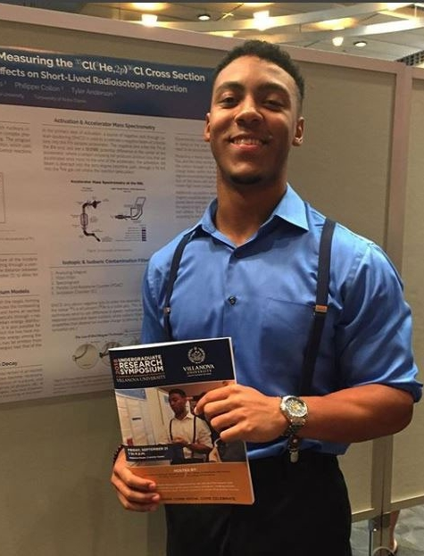 Connor Williams wearing a blue shirt and suspenders holding up a research paper at a conference