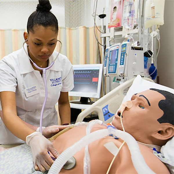 A female nursing student taking vitals as part of a simulation