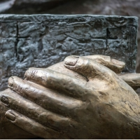 Bronze clasped hands holding a book