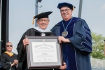 Irwin Medway holding diploma standing with Father Peter at Commencement
