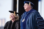 Anne Welsh McNulty standing with Father Peter at Commencement