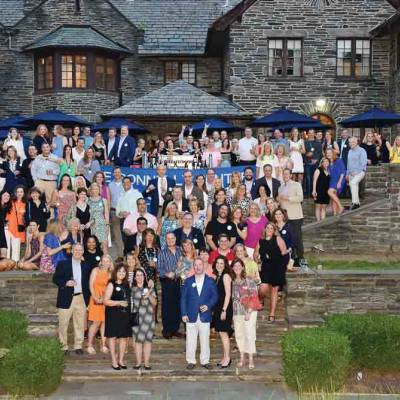Large group of Villanova Alumni standing along the stone steps and back lawn at the Inn at Villanova