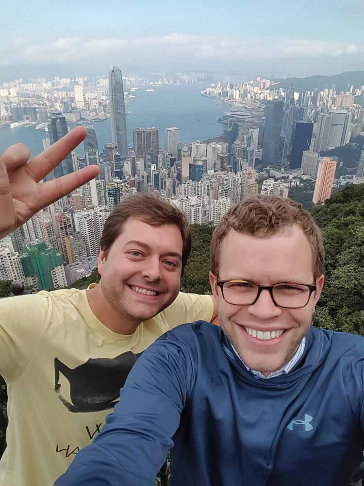 Paul Parisi and Joseph Martyn smiling with the skyline of Hong Kong behind them
