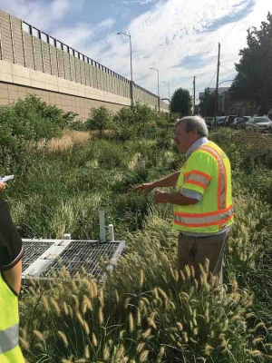 Faculty member in a high-visibility vest tests storm water