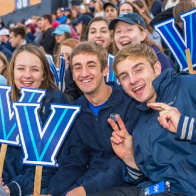 A group of Villanovans hold up signs of the Villanova V and put their V's up