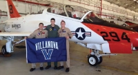 Kyle Lewis '14 COE, Brian Moscioni '15 COE and Chris Honeycutt '14 VSB holding Villanova flag in front of a T-45C Goshawk at Naval Air Station Kingsville in Texas