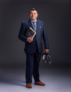 Luis Canales standing with book in one hand and running shoes in the other hand.