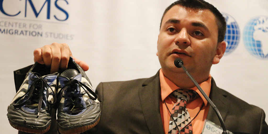 Luis Canales holding up his running shoes.