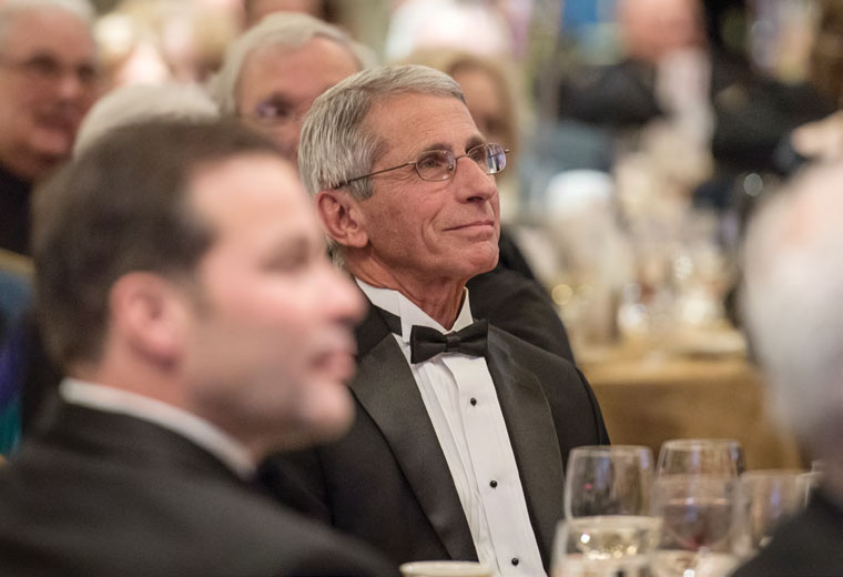 Smiling NIH Immunologist sitting at table during awards ceremony