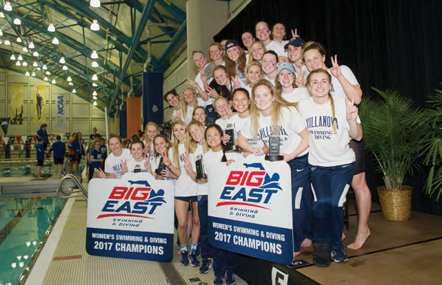 Women's Swimming and Diving teal standing in a group by the pool holding Big East Championship signs