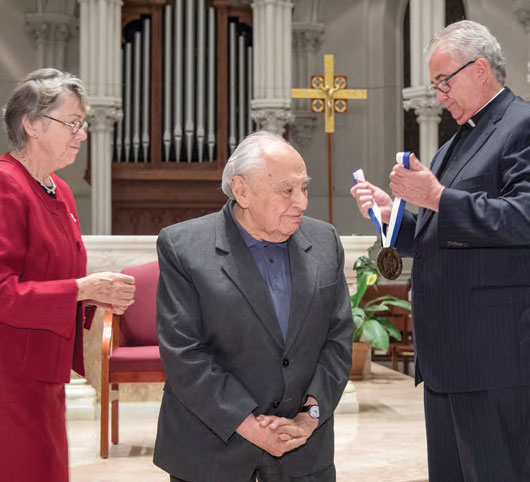 Gustavo Gutierrez stands to receive medal from Father Peter