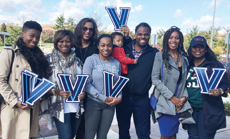 "Members of the Black Alumni Society at Homecoming standing together holding Villanova ""V"" signs and smiling."