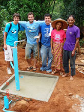 Rory Kotter, Christopher Philip, and Michael Matsushima stand behind one of the six tap stands that Villanova students and Thai villagers installed together.
