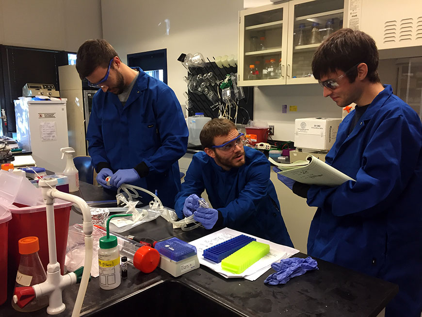 Graduate students Devon Zimmerman, Kyle Spivack and Matthew Nicholas analyze the cell culture bag for surface modifications.