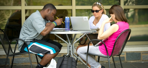 students sitting at a table on campus