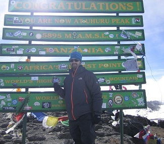 Carl Kapes displays a photo of his sons, Ryan and Brayden,  as he stands at the top of Mt. Kilimanjaro.