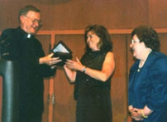 As Dean Fitzpatrick looks on, University President Rev. Edmund J. Dobbin, OSA presents Ms. Emily Riley of the Connelly Foundation with a token of appreciation after her announcement of its $4 million endowment of College of Nursing initiatives in celebration of the College's 50th anniversary. April 26, 2004.
