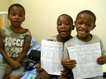 Young boys at St. Theresa's Home for Children hold their health screening record created by faculty Prof