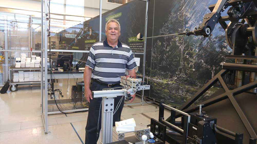 John Spitzer testing golf equipment, standing next to a testing machine.