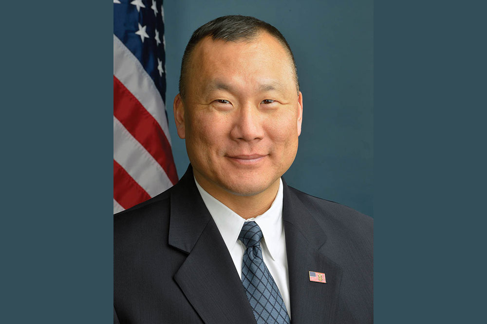 Headshot of Jin Kim in front of USA flag.