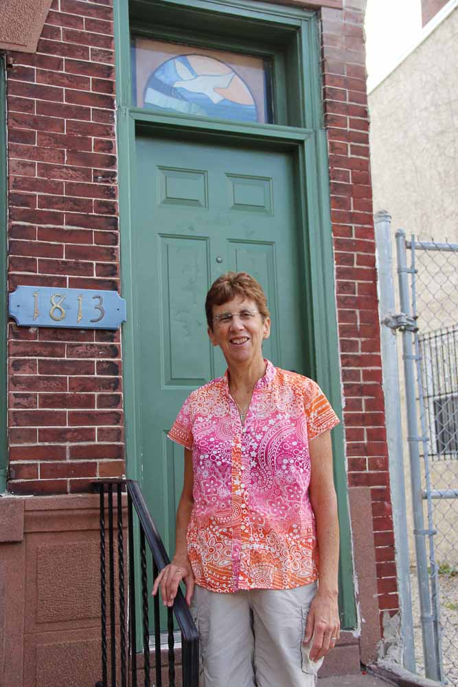 Mary Beth Appel standing outside a doorway.