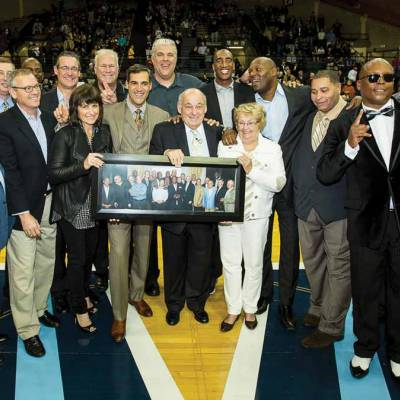 Members of the 1985 National Championship team standing on the basketball court holding a group photo.