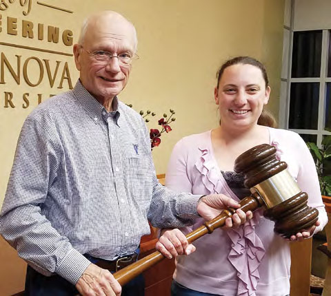 Bob Merkert '59 standing with Ashley Ferguson '09 both holidng a large gavel